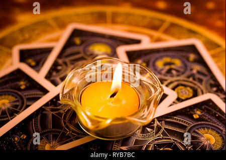 esoteric table with tarots and candle - Stock Image