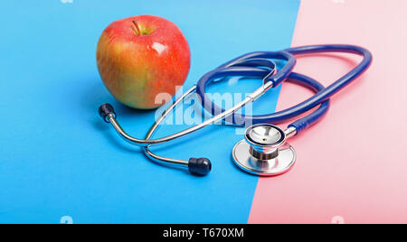 Stethoscope and apple between blue and red areas, the concept of the boundary of health and illness, healthy and unhealthy lifestyle. - Stock Image