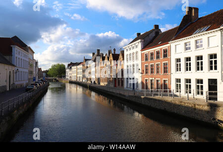 Scenic city view of Bruges canal with beautiful medieval colored houses, bridge and reflections at sunny day. - Stock Image