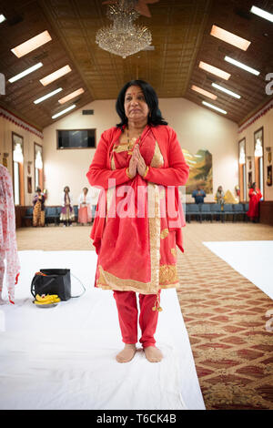 An attractive middle aged  Hindu woman in a beautiful sari with her hands clasped in a temple in Jamaica, Queens, New York City. - Stock Image
