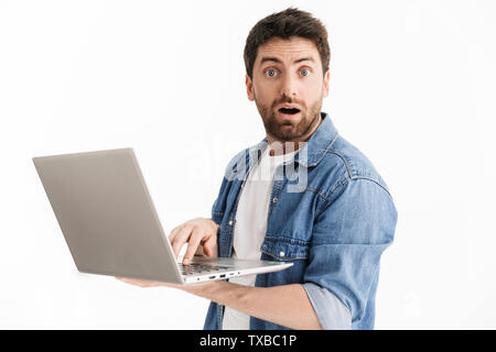 Portrait of an excited handsome bearded man wearing casual clothes standing isolated over white background, using laptop computer - Stock Image