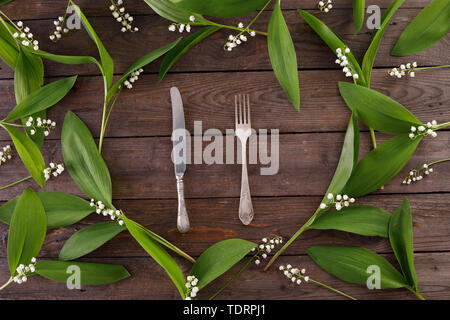 The decor of the flowers of lily of the valley on the background of vintage wooden boards. Vintage background with frame of flowers and place under th - Stock Image