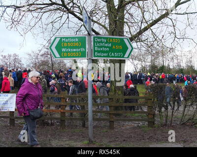 Ashbourne Shrovetide Football 2019. A spectator picks her way through the crowds and mud past a signpost to other local towns on Ash Wednesday - Stock Image