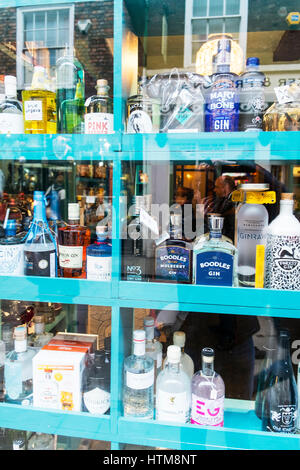 Gin shop gin bottles for sale in store window rare gin bottles rare variations if gins bottles of gin on display - Stock Image