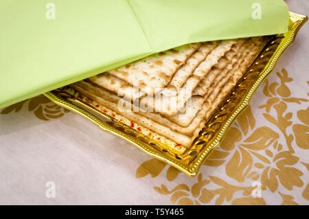 Several pieces of matzoh, traditional Jewish unleavened bread on a plate covered with a green napkin. Jewish Passover Pesach concept. - Stock Image