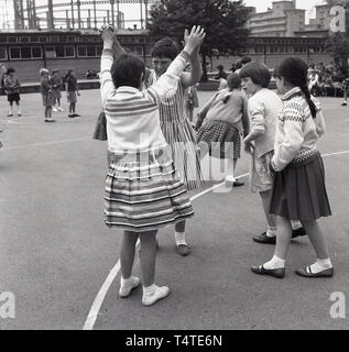 1960s, historical, Vauxhall, South London, school girls playing together outside in the playground, London, England, UK. - Stock Image