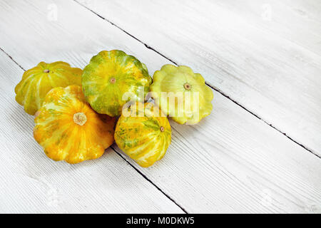Five yellow and green bush pumpkins on white wood background left. Garden,agriculture and farming concept. - Stock Image