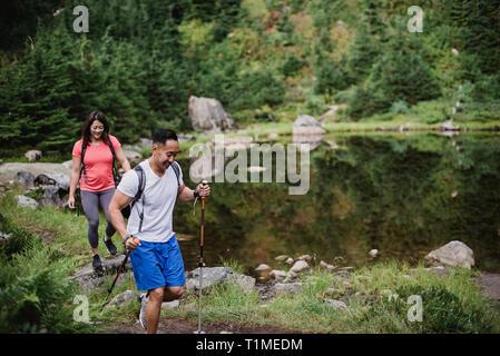 Couple hiking along lake in woods - Stock Image