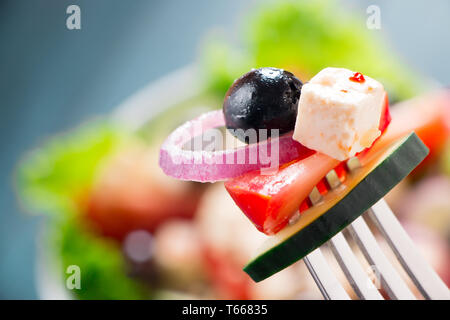 Close up of greek salad with tomato,  cucumber, purple onion, feta cheese and black olive in a fork - Stock Image