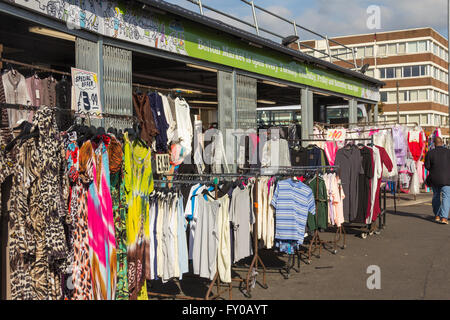 Outdoor stalls mostly selling clothing on Bolton market. - Stock Image