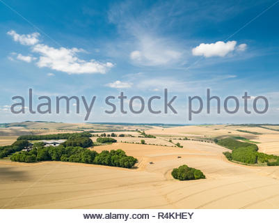 Aerial landscape view of summer farm wheat and barley harvest fields and blue sky - Stock Image