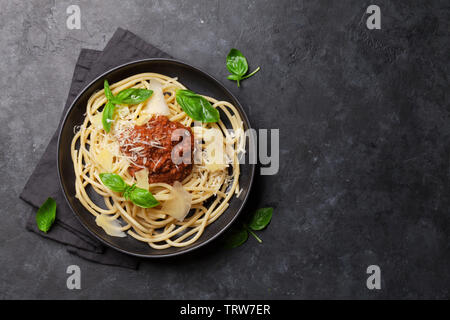Spaghetti bolognese pasta with tomato and minced meat sauce, parmesan cheese and fresh basil. Top view with copy space - Stock Image