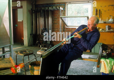 Glass maker at Orrefors preparing to blow red hot molten glass into fine crystal products - Stock Image