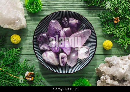 Polished Amethyst Stones with Smoky Quartz and Greenery - Stock Image