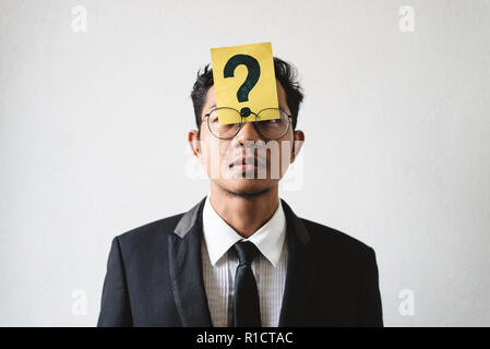Young Asian businessman with QUESTION MARK on his forehead. Concept of business solution, planning and problems - Stock Image