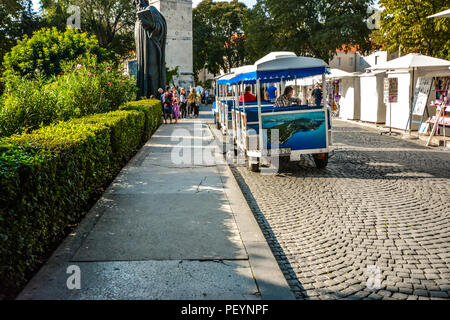 Tourists crowd around the statue of Gregory Nin as a cat scurries under a tourist tram outside the Golden Gate to Diocletian's Palace in Split Croatia - Stock Image
