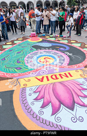 A member of Team India creates a floral carpet made from colored sawdust and decorated with flowers during the 8th Night Celebration marking the end of the Feast of St Michael in the central Mexican town of Uriangato, Guanajuato. Every year the town decorates 5km of road with religious icons in preparation for the statue of the patron saint to be paraded through the town. Uriangato became an international sensation after wowing Brussels with their floral carpet displayed at the Brussels Grand-Place during the Belgium Floral Carpet festival. - Stock Image