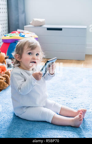 16 month old baby girl with cell phone. - Stock Image