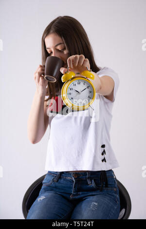 Young girl with retro clock in hand showing time and drinking coffee isolated on white background. Woman is blurred. Close up, selective focus - Stock Image
