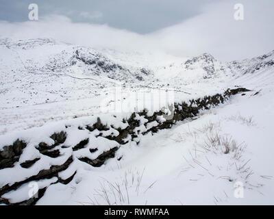 Dry stone wall near Ffynnon lugwy reservoir, Snowdonia, Wales in snow - Stock Image