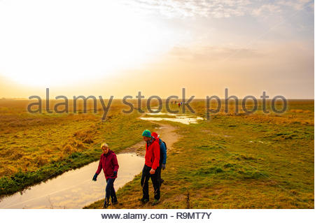 RSPB Marshside, Southport Beach, People walking off their Christmas excesses on a slightly misty Boxing Day afternoon at RSPB Marshside Nature Reserve as the light starts to fade in the Merseyside seaside town , Lancashire, England UK Credit: Christopher Canty Photography/Alamy Live News - Stock Image