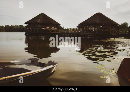 Bungalow with thatched roofs on the lake against the backdrop of boats and lilies in summer - Stock Image