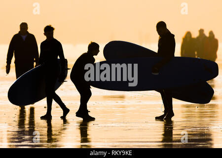 Surfers carrying surfboards silhouetted against late afternoon sunlight. - Stock Image