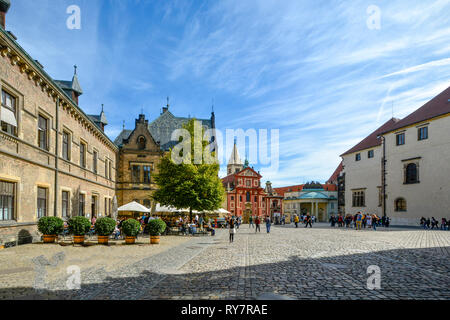 Tourists enjoy lunch at an outdoor cafe surrounded by colorful medieval buildings  inside the Prague Castle grounds in Prague, Czech Republic - Stock Image