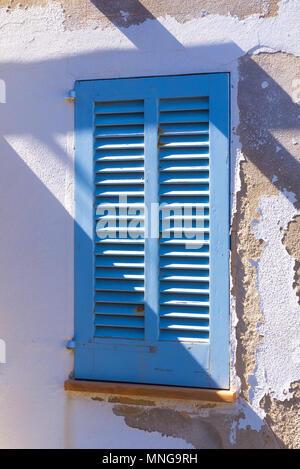 A blue window shutter adorns a house in Cala San Vincente on the Spanish island Mallorca. - Stock Image