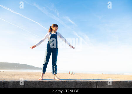 Happy little girl in overalls raising arms like a plane against the sky on the beach - Stock Image
