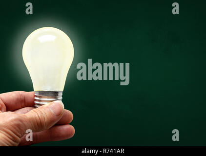 Man holding illuminated bulb with bare hands against chalkboard with copy space. Concept of bright idea, innovation, imagination, inspiration, vision. - Stock Image