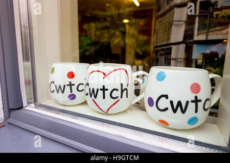 Three mugs with the Welsh language word Cwtch, meaning cuddle or hug in a shop window. - Stock Image