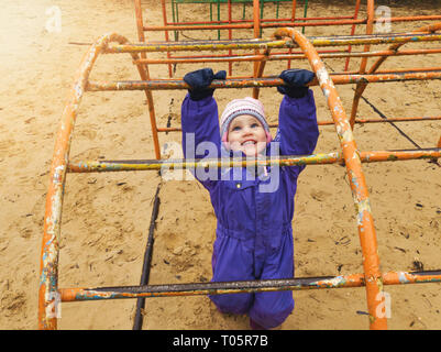 child playing at playground on cool spring day - Stock Image