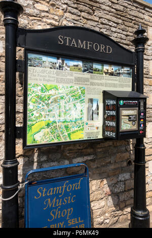 Tourist information sign and town map with dispenser, Stamford, Lincolnshire, England, UK - Stock Image