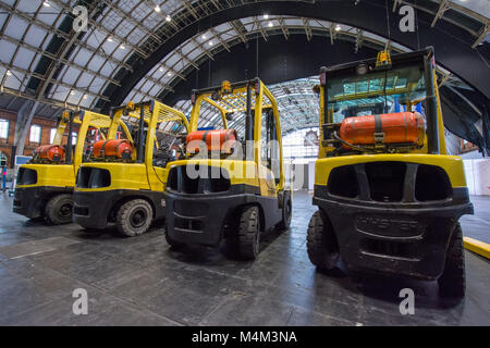 Four Forklift trucks lined up inside a large arena © Jeremy Graham-Cumming - Stock Image