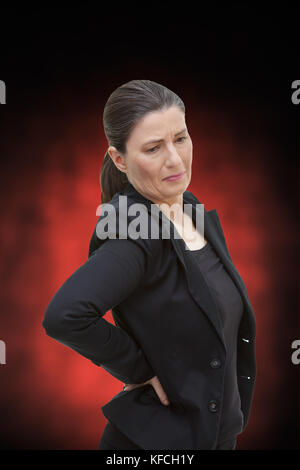 Middle aged woman with chronic pain syndrome fibromyalgia suffering from acute backache, on red and black background - Stock Image
