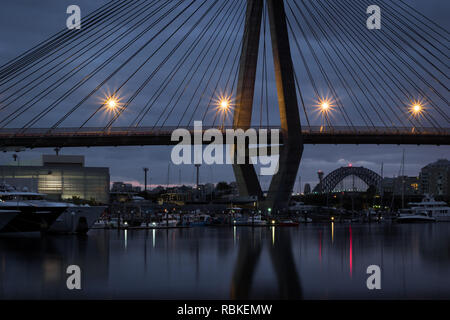 The sydney harbour bridge nestling under the anzac bridge on a cloudy morning - Stock Image