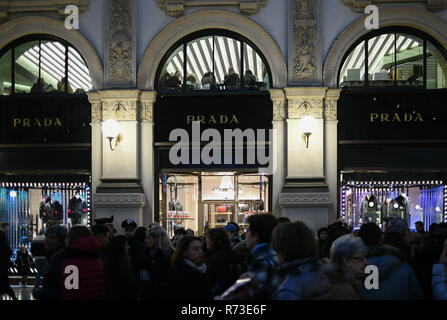 Milan, Italy - December 7, 2018: Crowd of people and tourists shop for Christmas in front of the shop windows of the PRADA luxury boutique store - Stock Image