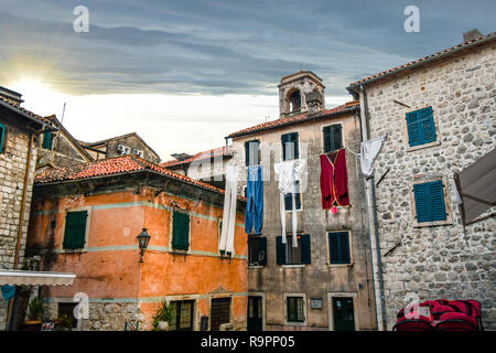 An oversized display of laundry hangs over a small village square near a cafe in the medieval city of Kotor, Montenegro. - Stock Image