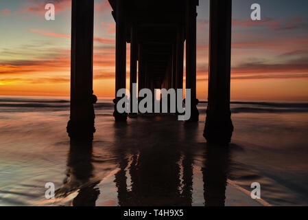 Brilliant sunset with drifting colorful clouds with a silhouette of the cement Scripps Pier with the tide coming in, La Jolla, San Diego, CA, USA. - Stock Image