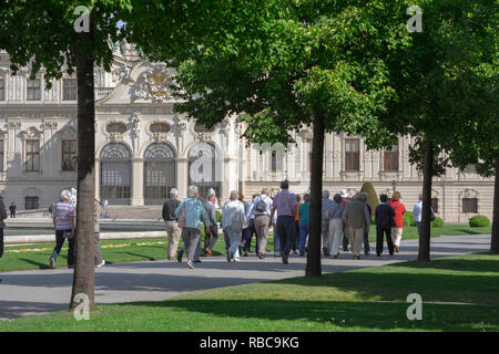 Tour group summer, visitors to the Schloss Belvedere Palace in Vienna tour its famous landscaped gardens, Wien, Austria. - Stock Image