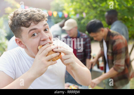 Portrait hungry teenage boy eating hamburger at backyard barbecue - Stock Image