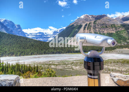Focus on a tower viewer or binoculars at a rest stop on the Icefields Parkway to allow visitors to take a closer look at the Stutfield Glacier in Jasp - Stock Image