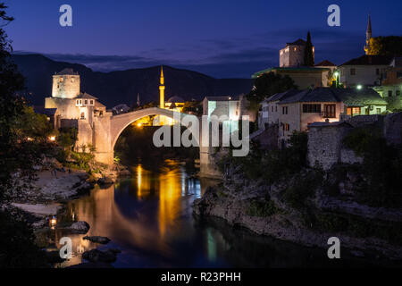 Night time view of the city of Mostar lit up along the river, featuring the rebuilt arched bridge: 'Stari Most'. - Stock Image