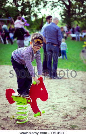 Young boy with face paint standing on a horse - Stock Image