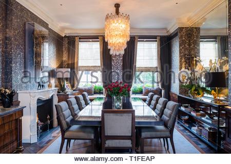 Lit chandelier in dark dining room - Stock Image
