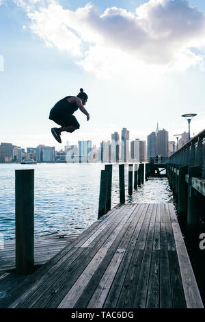 USA, New York, Brooklyn, young man doing Parkour jump from wooden pole in front of Manhattan skyline - Stock Image