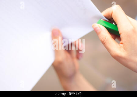 Office staple gun stapling paper in hand of young lady. - Stock Image
