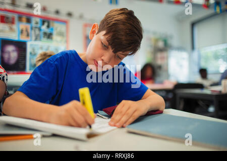 Focused junior high school boy student using highlighter, doing homework in classroom - Stock Image
