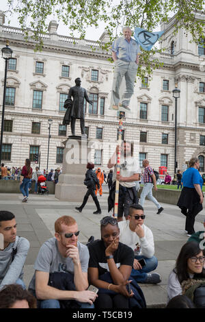 An image of veteran wildlife and environmental broadcaster Sir David Attenborough is held high in Parliament Square during the week-long protest by climate change activists with Extinction Rebellion's campaign to block road junctions and bridges around the capital, on 23rd April 2019, in London England. - Stock Image